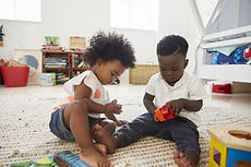 two black children playing in room together.jpg