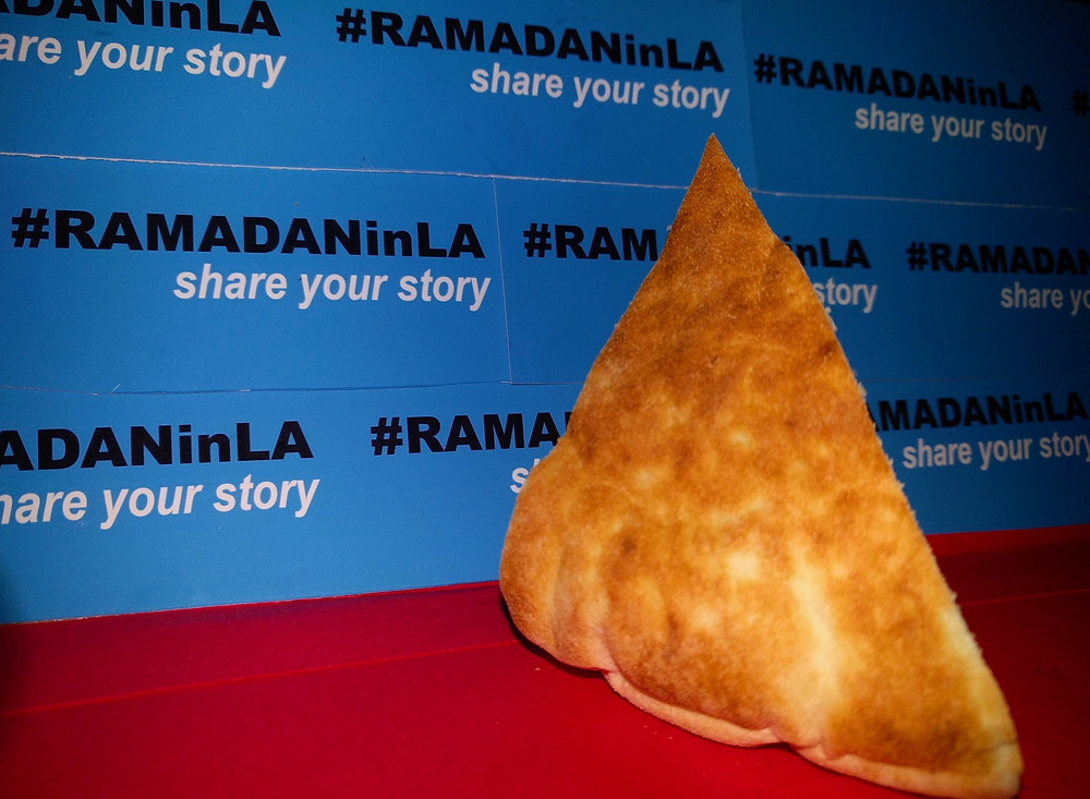 Pita chip on the red carpet in front of a step and repeat of #RAMADANinLA share your story