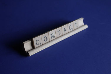scrabble pieces spelling contact us with blue background