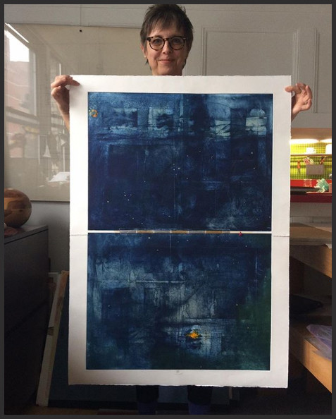 """A photograph of Karin Bruckner holding her art work 'GoldCoast' Large printmaking composite Partially wiped etching and monoprint with metal leaf On white BFK Rives printmaking paper 30"""" x 40"""" 2017 - © Karin Bruckner - Twitter Art Exhibit"""