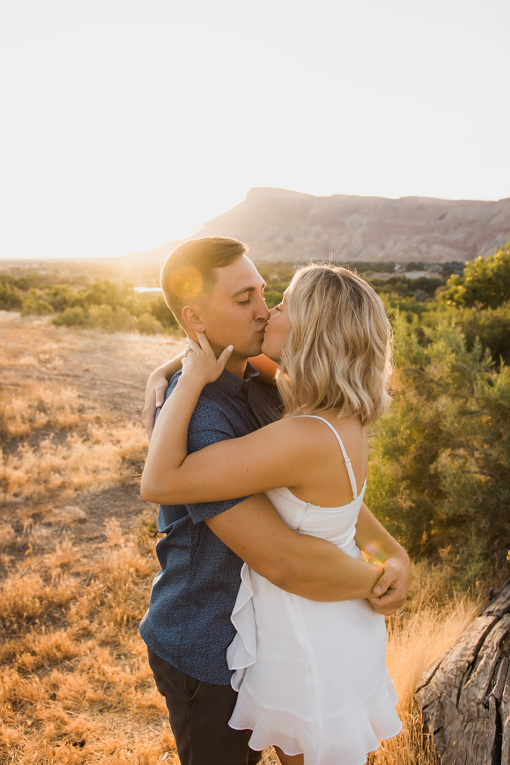 Mt Garfield sunset view with kissing couple engagement photos Palisade Colorado