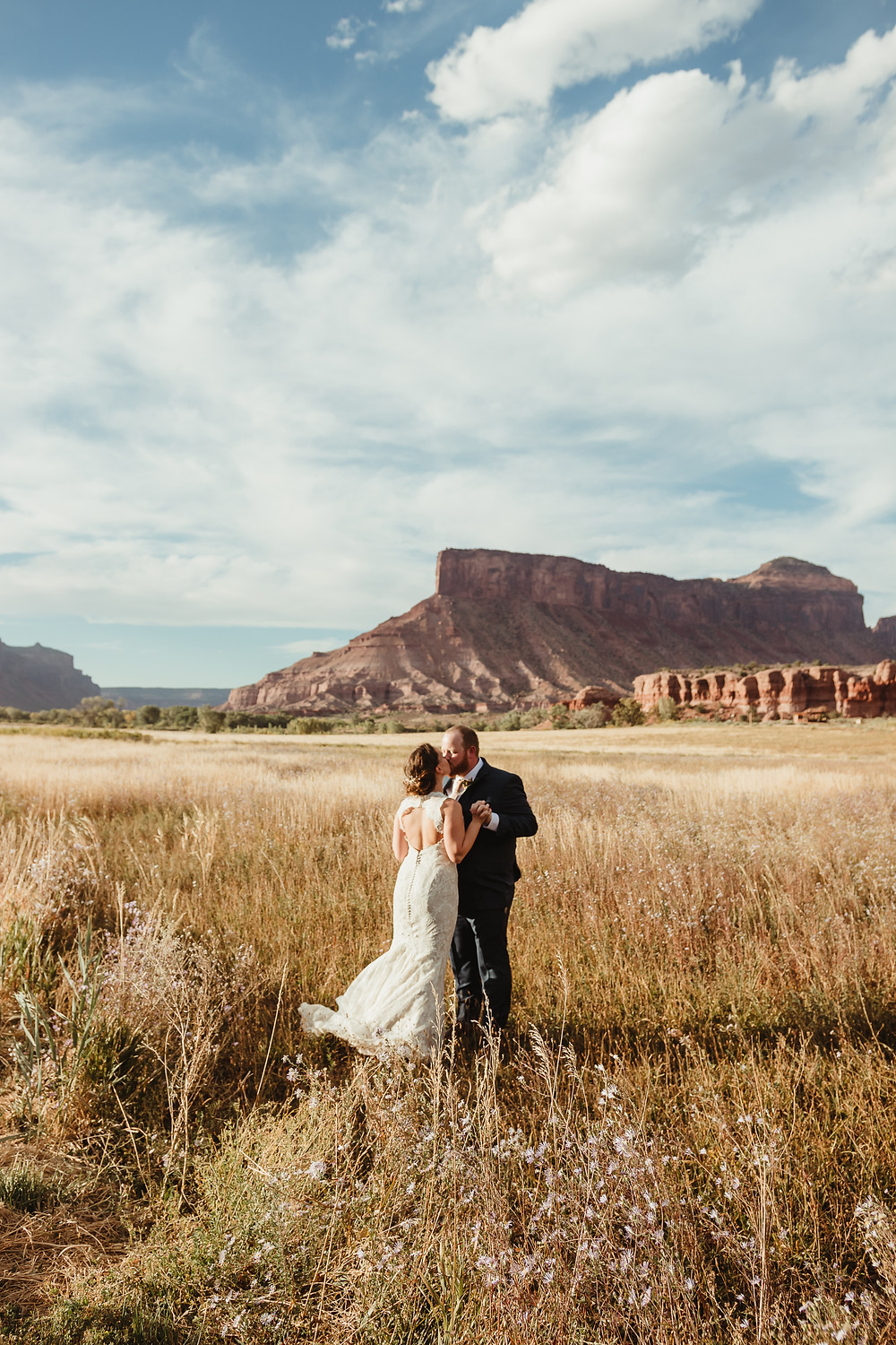 Gateway Canyons Resort Colorado elopement ceremony intimate bride and groom kiss open field red rock canyon