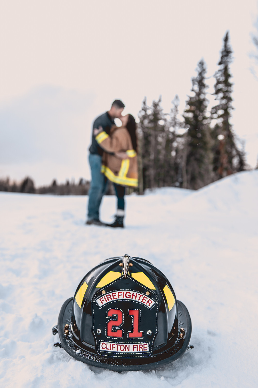 Firefighter engagement photos helmet snowy Colorado mountains Grand Mesa Lakes Lodge winter