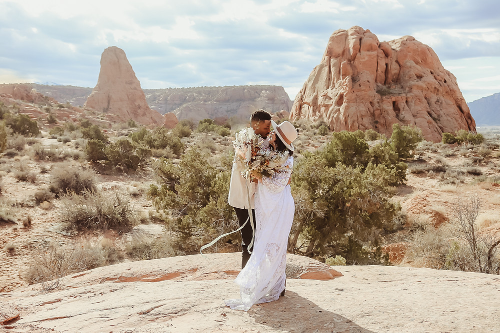Moab Utah elopement couple bride and groom red rocks desert eloping Colorado photographer wedding kiss