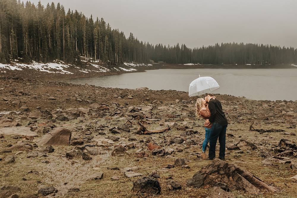 Colorado mountains engagement photos rainy day Grand Mesa couple kissing