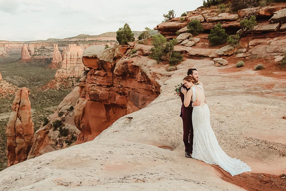 Colorado National Monument intimate elopement bride and groom elope desert scenery Bookcliff Overlook hug