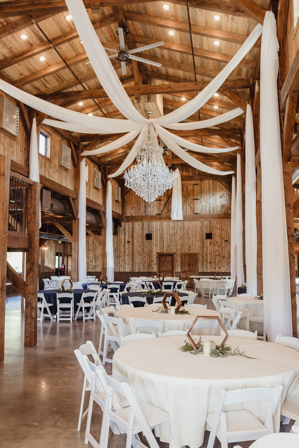 Orchard River View Palisade Colorado barn wedding venue indoor table settings chandelier drape