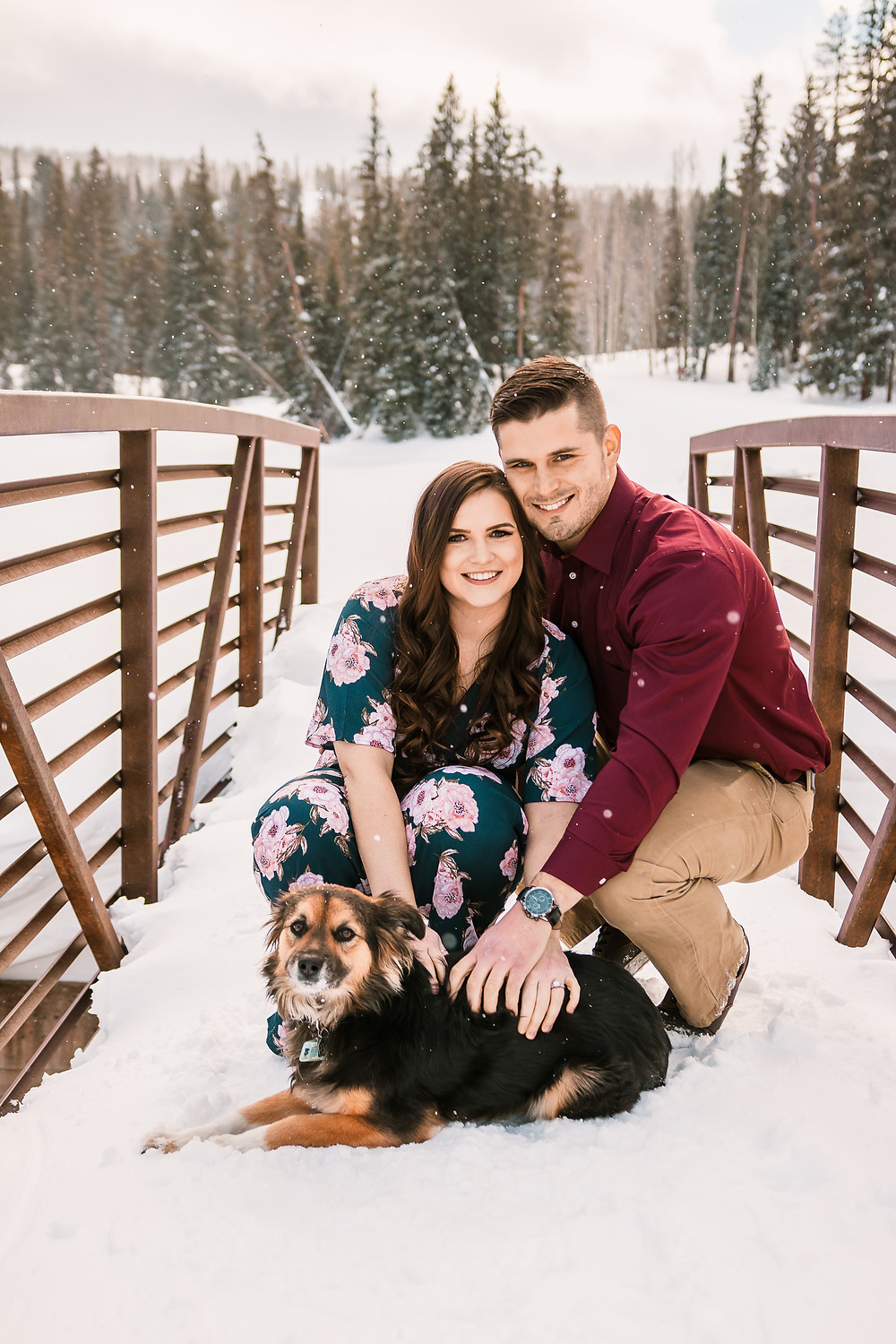 Winter snow falling engagement photos with dog Colorado Mountains snowy trees Grand Mesa Lakes lodge