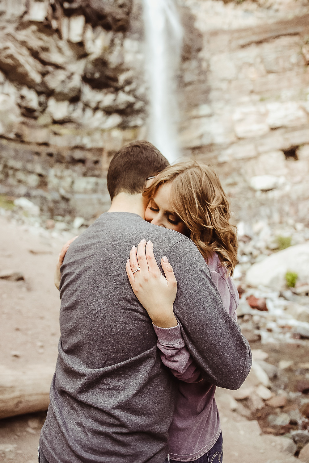 Beautiful engaged couple hugging under waterfall Cascade Falls Ouray Colorado