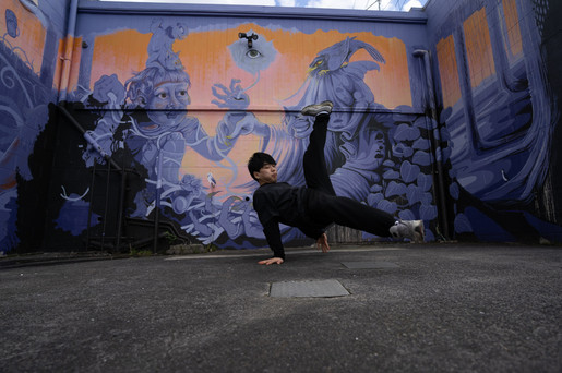 B-boy Simba breakdancing in front of Erin Forsyth's mural painted at Bradley Lane Project 2017.