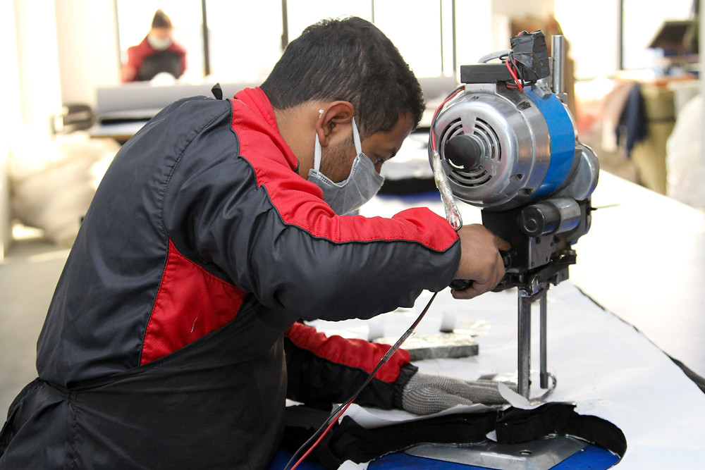 Production worker at Purnaa cutting fabric using cutting tool