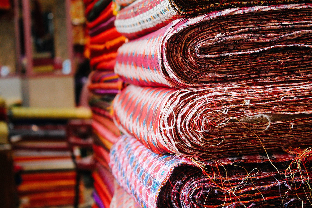 Dhaka fabric stacked up in a Nepali shop - showing the differing Nepali fabrics