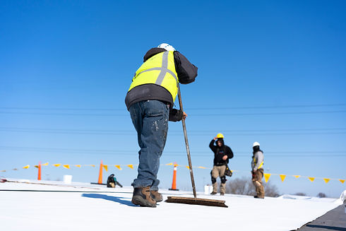 Roofing construction worker installing a flat roof. Bright blue sky in the background..jpg