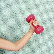 young-woman-lifting-dumbbell--against-ti