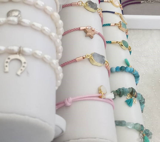 A selection of beaded gemstone and pearl bracelets with charms and tassels.