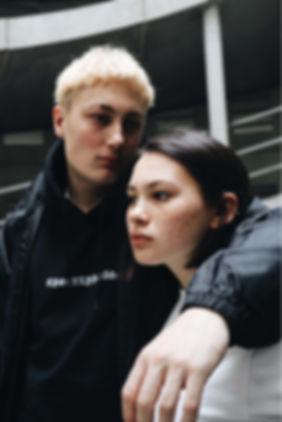 Mädchen und Junge gucken weg mit schwarze Hoodie
