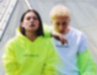 Mädchen und Junge auf dach im noen gelben hoodie