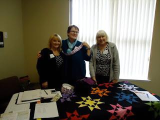 Bev Ikeda, Carol Cure, And Cheryl Hudson Displaying Quilt Benefitting FEDICE