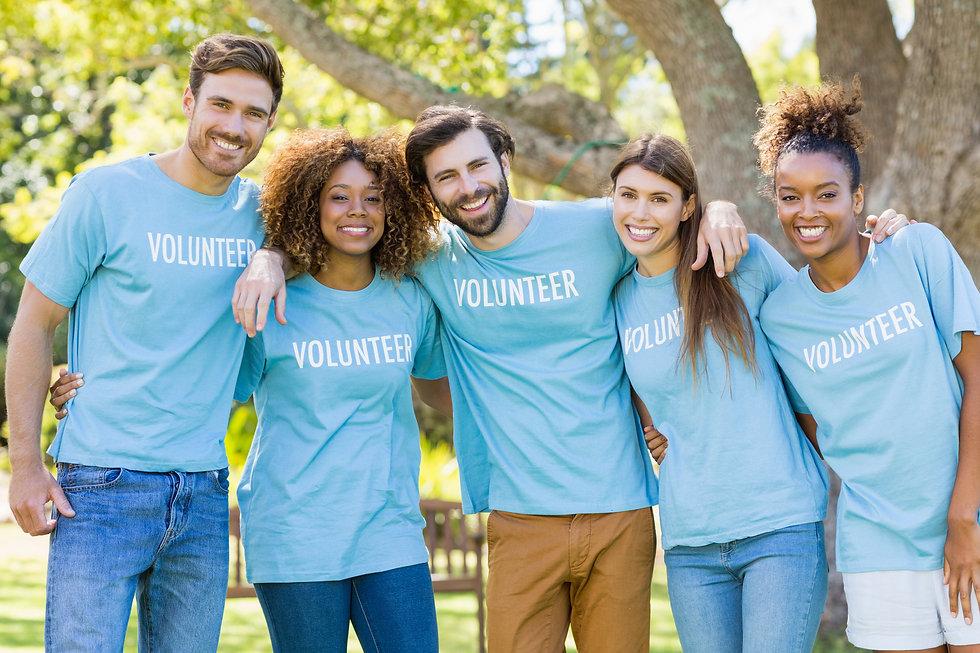 Portrait of volunteer group posing in pa