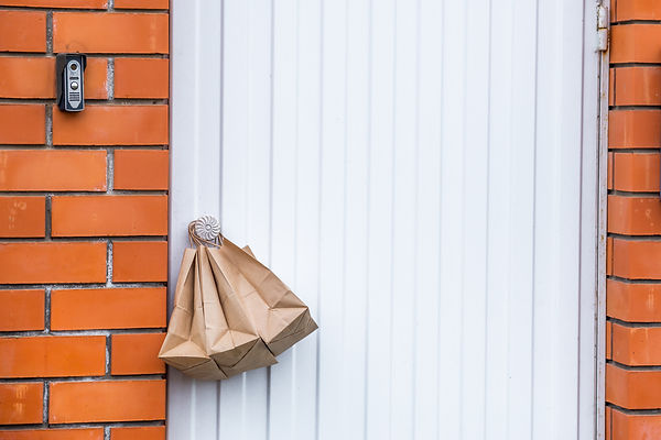The concept of safe delivery in close-up. paper bags with food on handle of front door nea