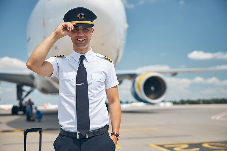 cheerful-young-man-airline-worker-touching-captain-hat-smiling-while-standing-airfield-wit