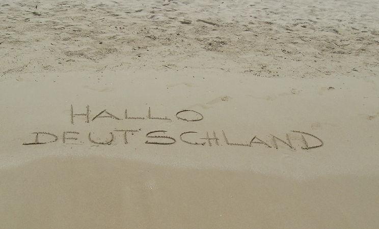 Hallo Deutschland wurde in den feuchten Sand am Strand von West Bay geschrieben