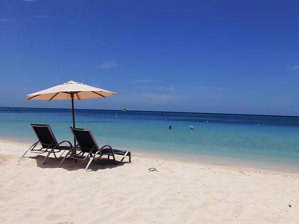 Ein Sonnenschirm und zwei Sonnenliegen am Strand in West Bay, Roatan und 2 Personen im Wasser