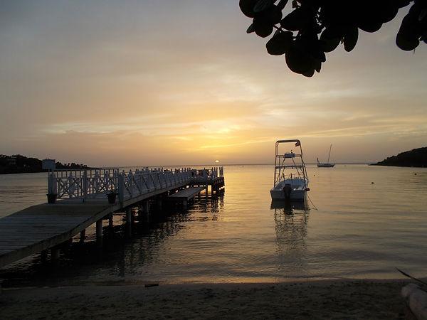 Sonnenuntergang in West End, im Vordergrund ein Tauchboot neben einem Anlegesteg, im Hintergrund ein Segelboot