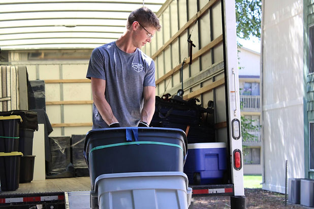 man who works for a moving company using a hand truck to load a moving truck