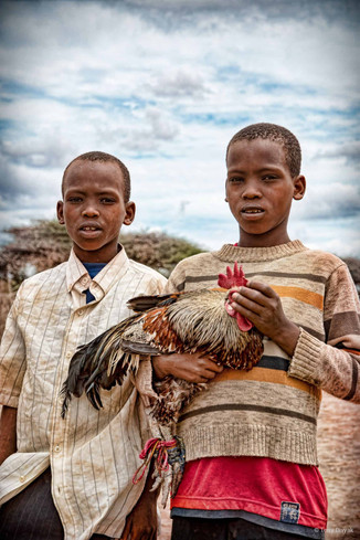 Boys with a chicken at market in Tanzania