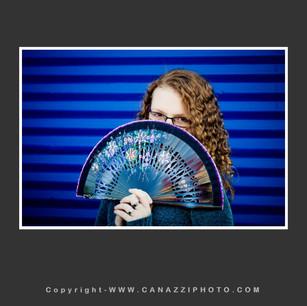 High School Senior Gal with fan in front of blue metal door in Portland Oregon_320.jpg