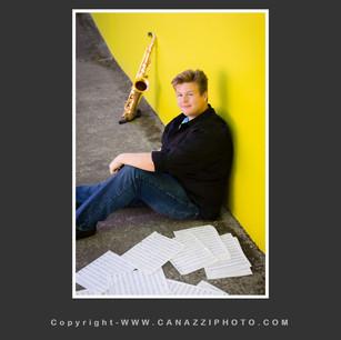 High School Senior Guy sitting with saxophone against yellow wall in Portland Oregon _311.jpg