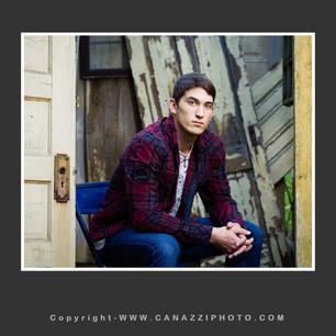 High School Senior Boy seated with old rustic doors Vancouver Washington_142.jpg