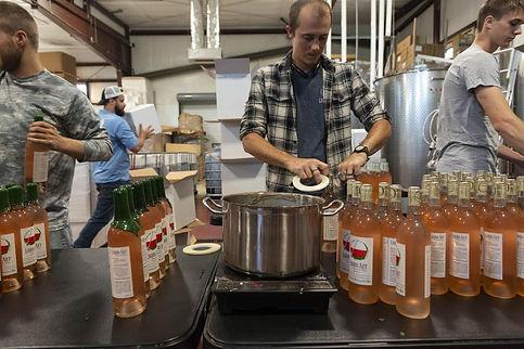 production team bottling wine at Liquid Art Winery in Manhattan, KS