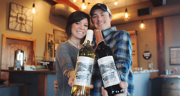 Owners Dave & Danielle holding bottes of wine in the Tasting Room at Liquid Art Winery in Manhattan, KS