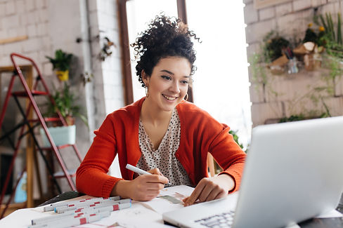 Young smilng woman with dark curly hair sitting at the table happily working on laptop dra