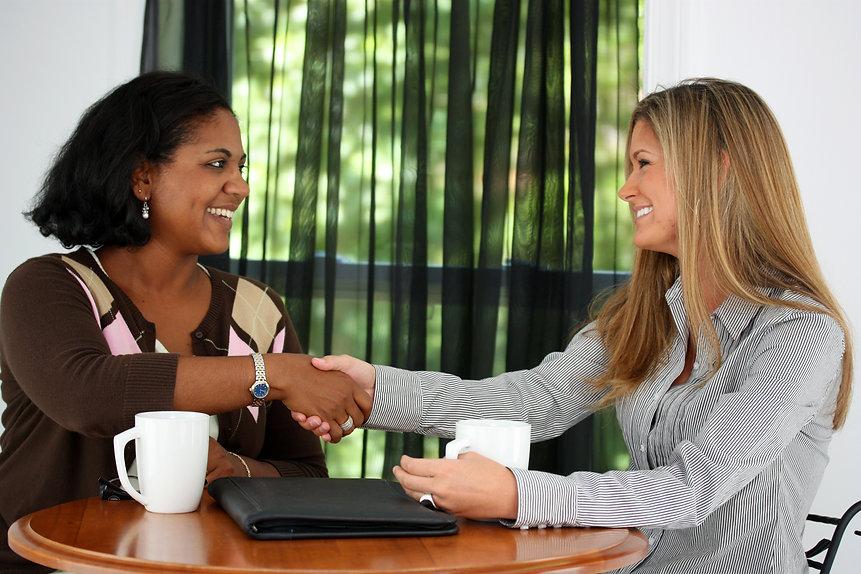 Two Women Shaking Hands In An Office.jpg