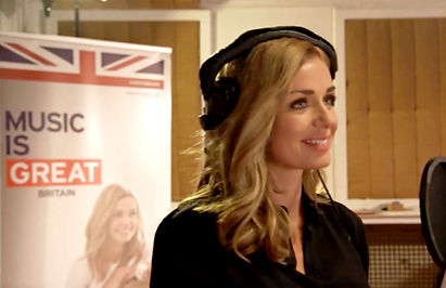 Katherine Jenkins in a recording studio in front of the Music is Great logo