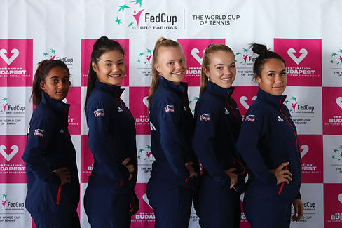 Five people posing in front of the Fed Cup branding