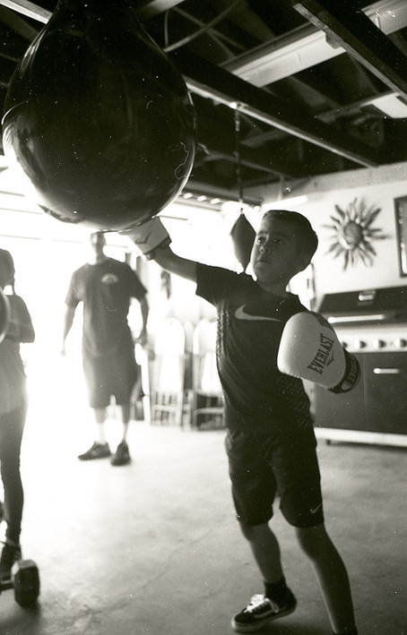 """Jayden Aguayo practicing his boxing skills at his Grandfathers gym 4 Corners Boxing Club. That is his Grandfather Jesse """"Rebel"""" Aguayo in the background watching his Grandson with so much pride. Jesse is an old friend of mine who is a real good person doing good things for the youth around him and for the future of boxing. LA CA 2018"""