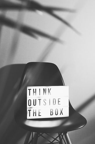Stuhl mit Schild think outside the box schwarz weiß