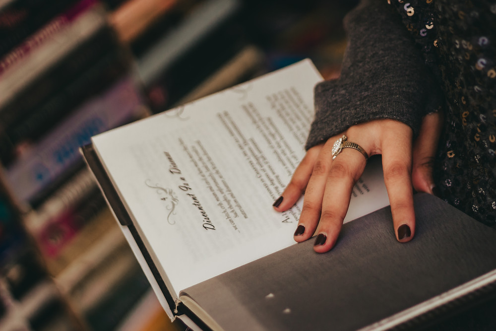 A woman's hand with black nail polish, a ring on her middle finger, wearing a long-sleeved sweater that covers most of her hand, holding open a book.