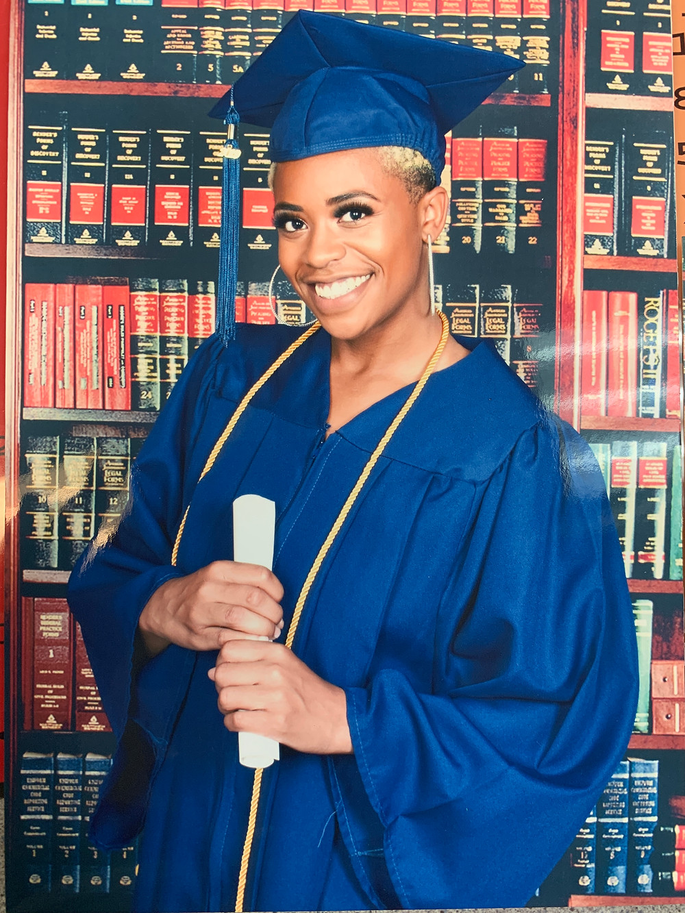 Black girl in graduation gown holding diploma behind a background of books.