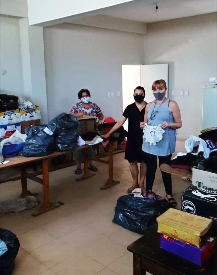 Voluntarias clasiificando las donaciones de ropa y calzado