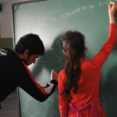 Niños escribiendo en un pizarrón.