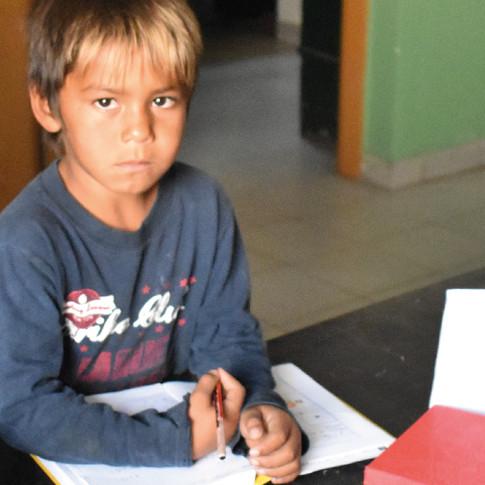 Niño con un papel y lapiceras. Expresión seria.