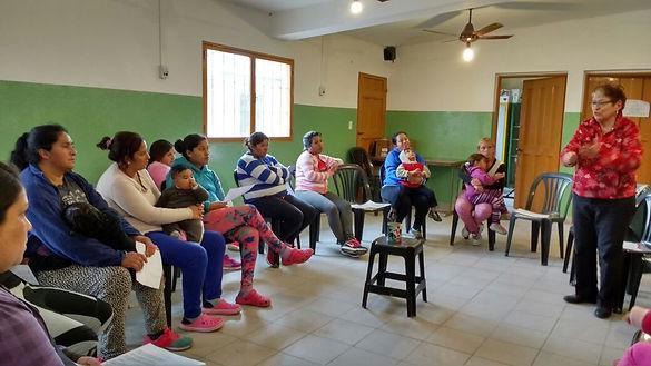 Grupo de personas sentados en ronda, algunos de ellos con niños.