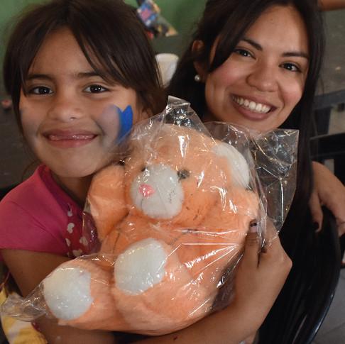 Niña junto a una joven sosteniendo un peluche en una bolsa de regalo