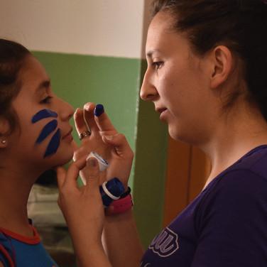 Muchacha pintando la cara de una niña con color morado.