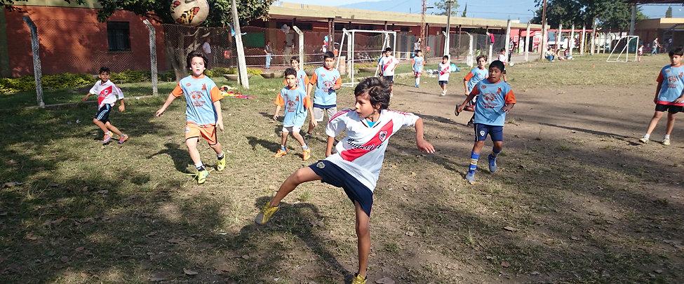 Grupo de niños jugando al fútbol al aire libre